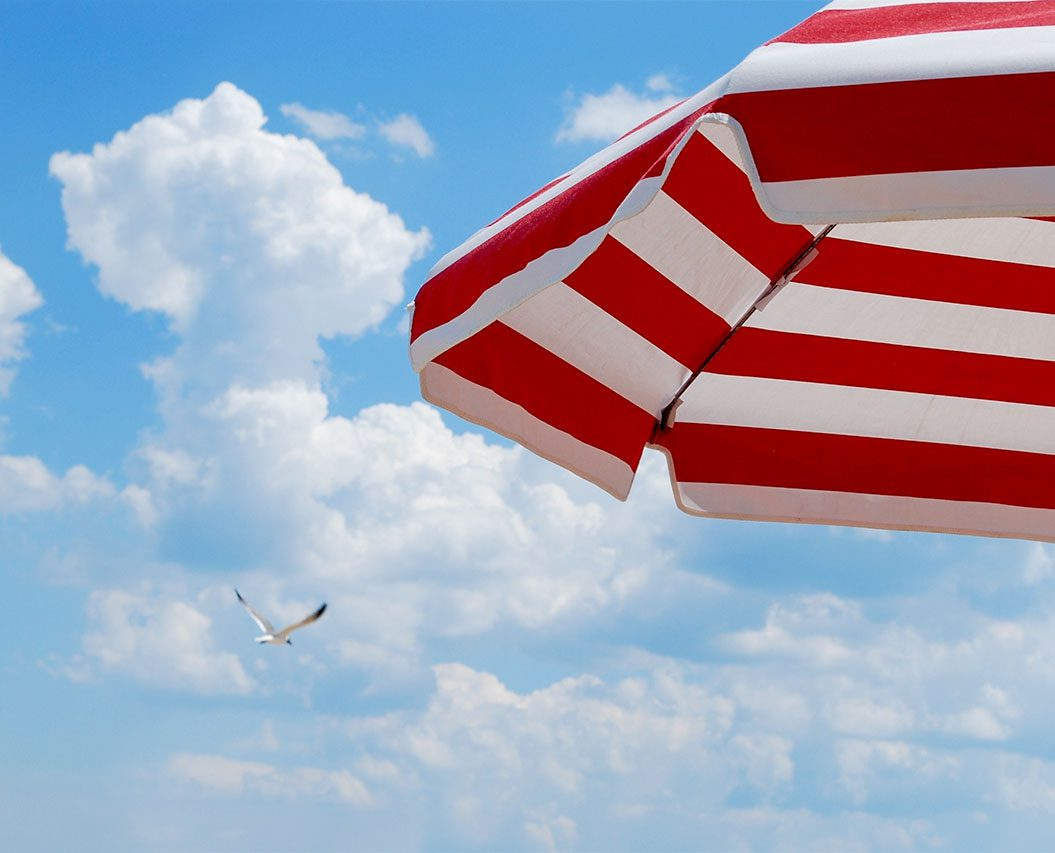 red and white striped parasol against blue sky