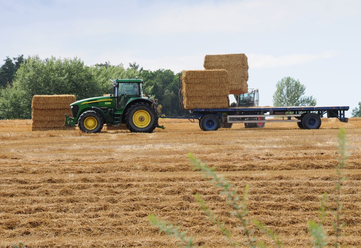 tractor driving through a field with bales of hay on the trailer